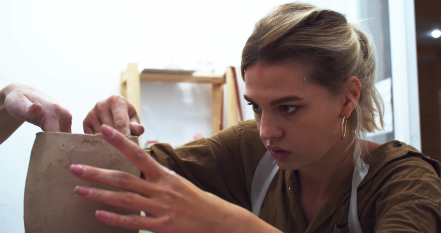Close up portrait of serious concentrated blonde woman learning to create handmade clay flower pot with teather in craft studio. Beautiful young female hands sculpting. Traveling art business. | Shutterstock HD Video #1042593391