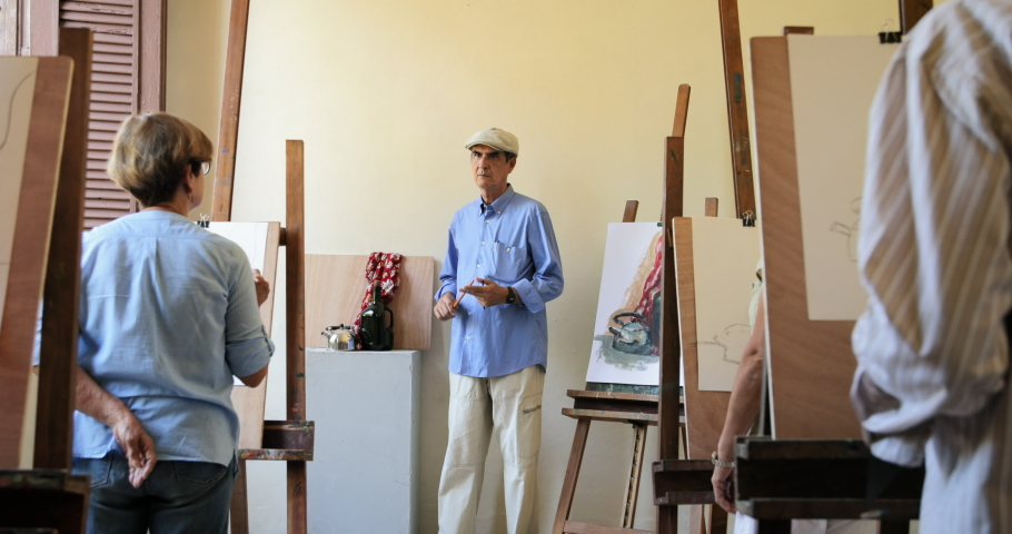Elderly people painting for hobby. Group of active seniors at art school. Leisure activity, lifestyle, recreation, passion. Old man at work as teacher, teaching technique to students. Slow motion | Shutterstock HD Video #1042704421