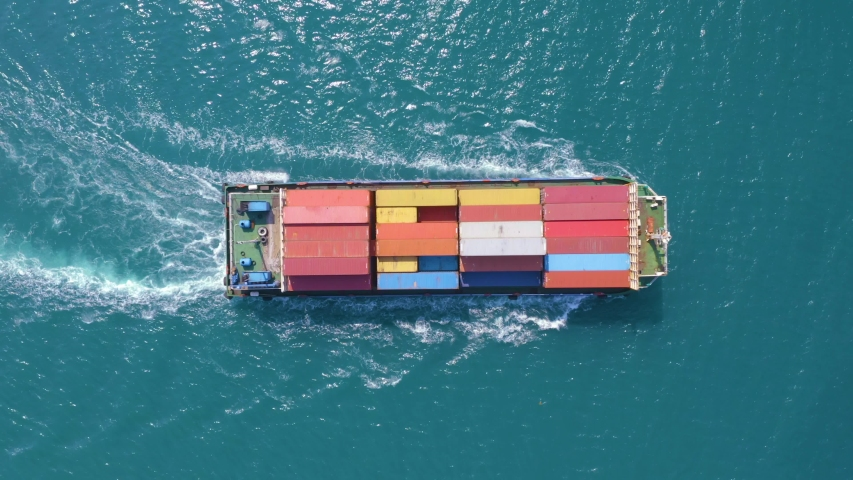 Top down Aerial View of a large container ship sailing at the sea for transporting shipments to other countries   | Shutterstock HD Video #1042723411