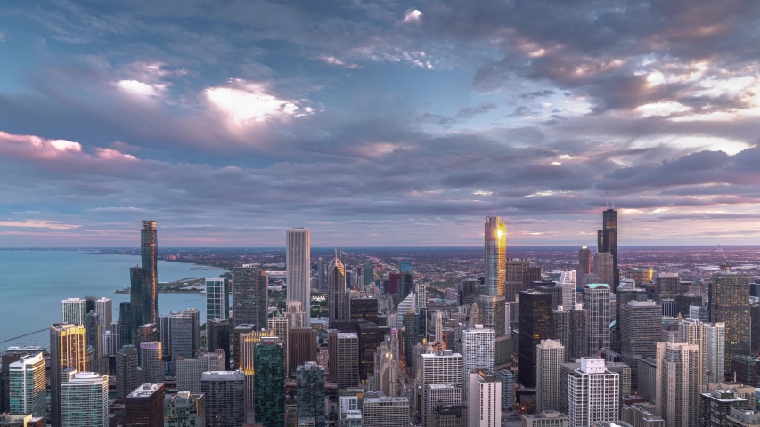 A beautiful aerial skyline panoramic sunset day to night zoom in time lapse of downtown Chicago with Lake Michigan and colorful pink and blue clouds as the sun sets and lights come on in the city.