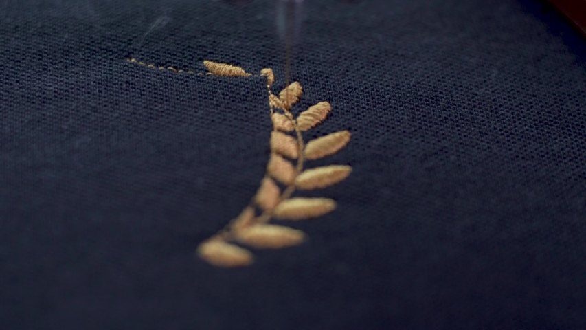 Extreme close up of Sewing needleing at a very high speed, completing a golden wreath on black fabric. | Shutterstock HD Video #1042754641
