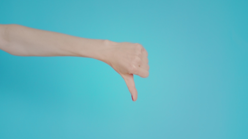 Woman's hand shows finger down, like or dislike, gesture on blue background. Copy space for advertisement. With place for text or image. Advertising area, mock up. Hand doubts the decision | Shutterstock HD Video #1042768231