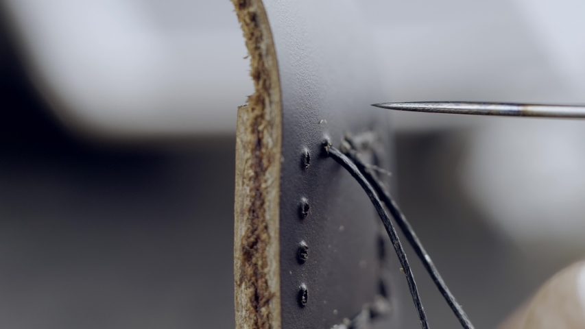 The master of working with leather flashes the strap with black thread. macro 4k   Shutterstock HD Video #1042812901