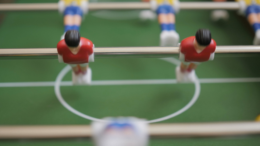Friends Playing Table Soccer Game Closeup. People playing in table football or kicker with miniature players. Slow Motion. Shallow DOF. Playing Football Soccer on game table. Close Up. | Shutterstock HD Video #1042905601