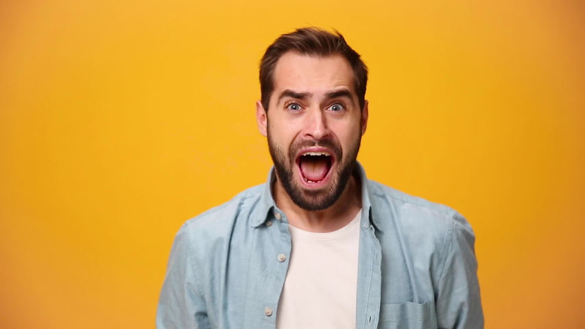 Handsome unshaven bearded young guy 20s in denim shirt white t-shirt isolated over yellow background in studio. People sincere emotion lifestyle concept. Looking at the camera scream win enjoy delight   Shutterstock HD Video #1042986751