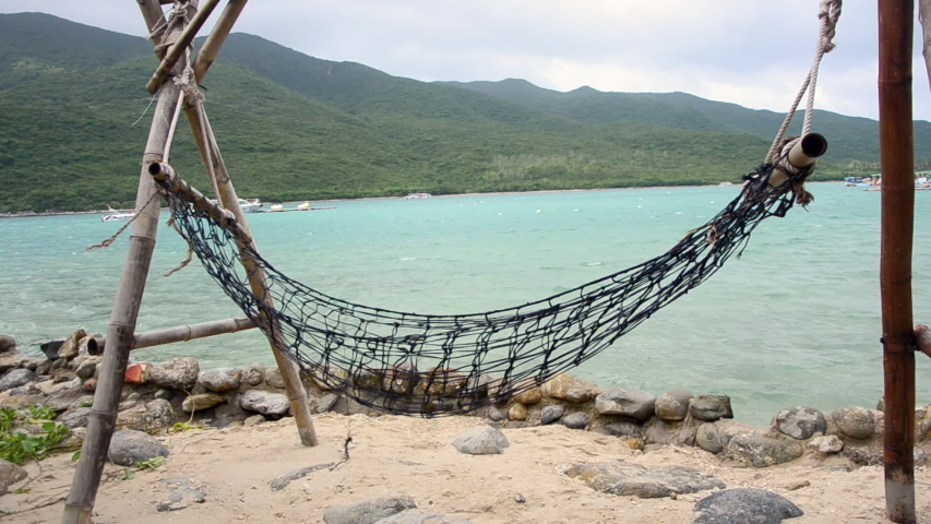 On the ocean coast, a beach hammock swaying in the wind and on small waves. On the horizon of the island, speed boat, jet skis. | Shutterstock HD Video #1043235271