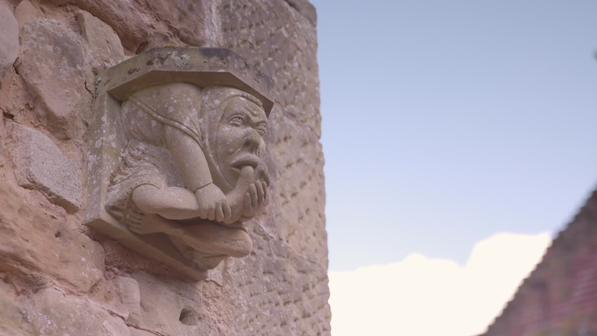 A daylight low angle shot of bracket attached to a stone wall featuring a carved sculpture of a grotesque human figure. | Shutterstock HD Video #1043331211