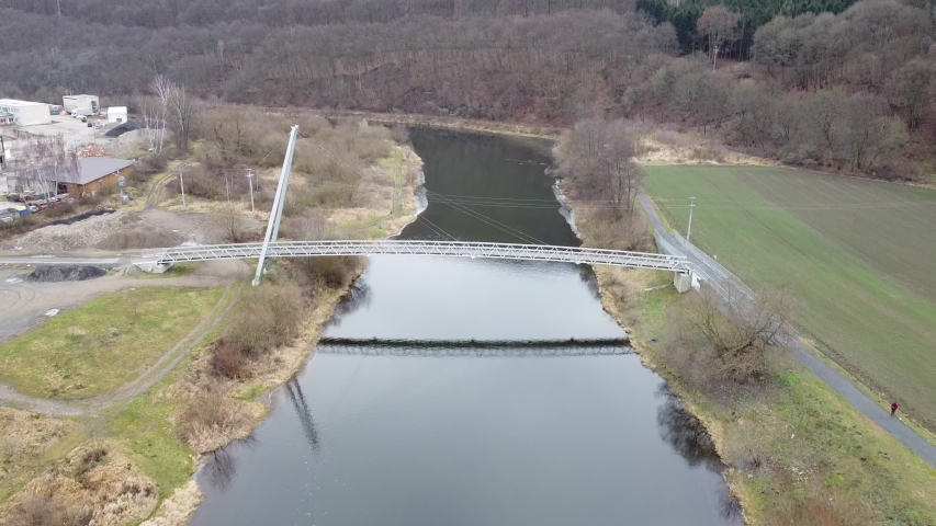 Moving the camera away from the bridge over the Berounka River in the village of Hýskov. Aerial view of the bridge. Winter without snow in the Czech Republic. | Shutterstock HD Video #1044172711