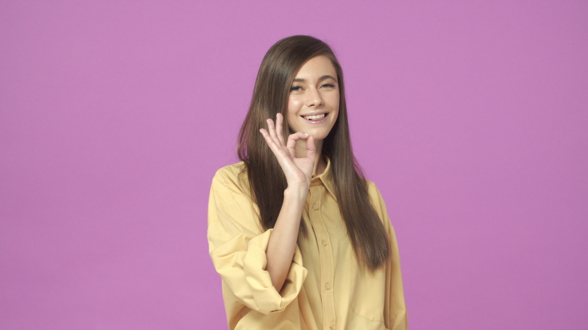 Dont worry, everything alright. Slow-motion cute, confident young female coworker have all good, under control, assuring work done great, wink and make okay gesture, agree, approve plan | Shutterstock HD Video #1044719371