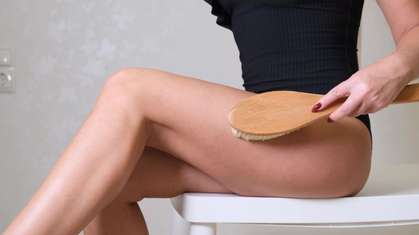 Woman massaging the skin of her legs with a dry massage brush on a white background. The girl is fighting cellulite | Shutterstock HD Video #1044766561
