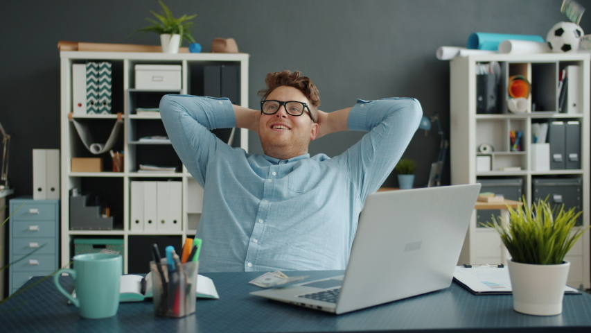 Slow motion of lots of money falling on handsome guy in office sitting at desk alone enjoying wealth. Happiness, rich youth and financial luck concept.   Shutterstock HD Video #1044817351