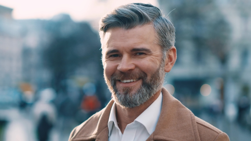 Extrime close up view of attractive middle aged man looks to the camera and smile in city center street success business outdoor portrait serious elegant feel happy great morning slow motion   Shutterstock HD Video #1044823621