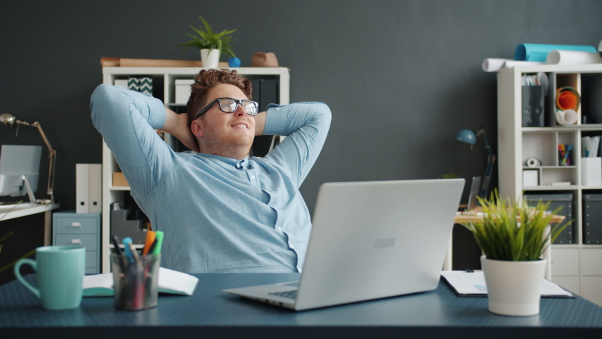 Entrepreneur attractive guy is relaxing in chair in office while money banknotes are falling down from above. Happy young people, wealth and business concept.   Shutterstock HD Video #1044824191