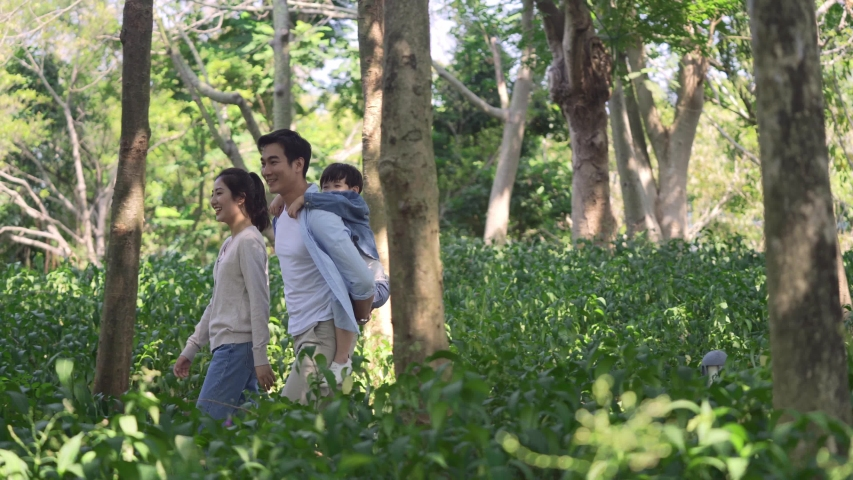 Happy asian family with one child walking through woods in park   Shutterstock HD Video #1044871681