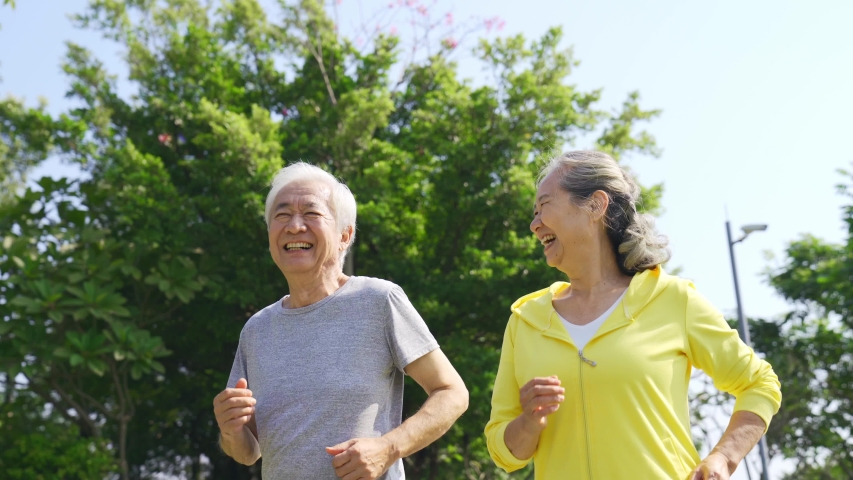 Happy senior asian couple jogging outdoors in a park   Shutterstock HD Video #1044871741