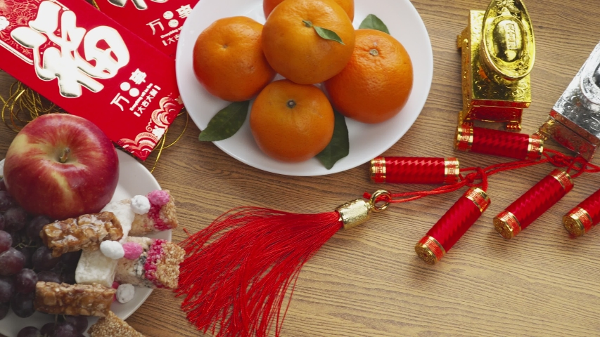 Flat lay Chinese new year festival decorations with orange apple grape and red packet. Texts appear in image meaning good fortune   Shutterstock HD Video #1044892771