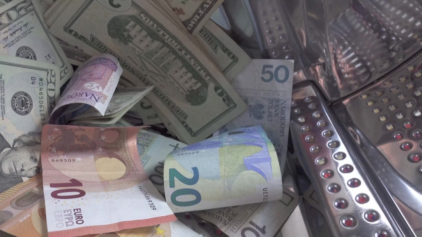 Money laundering concept. Euros, dollar and other currencies banknotes turning in washer. | Shutterstock HD Video #1044899701