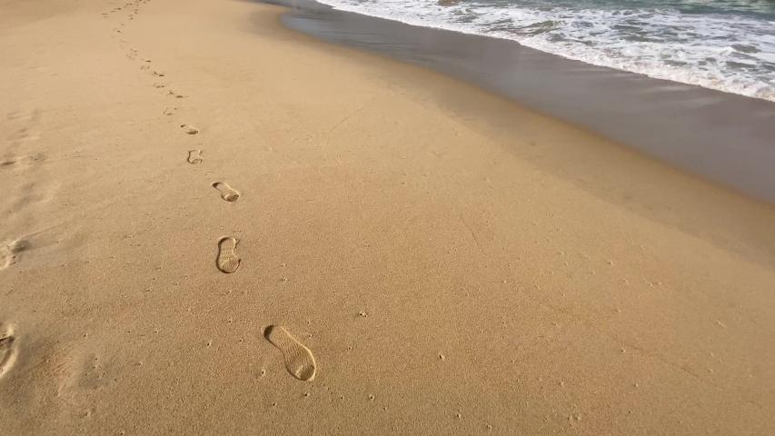 Walk on the sandy beach along the footprints on sand. Uminonakamichi Coast | Shutterstock HD Video #1044928021