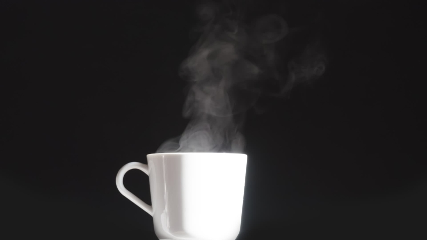 White Cup with a Hot Drink. Brightly lit white mug from which hot steam rises slowly on a black background | Shutterstock HD Video #1044930721