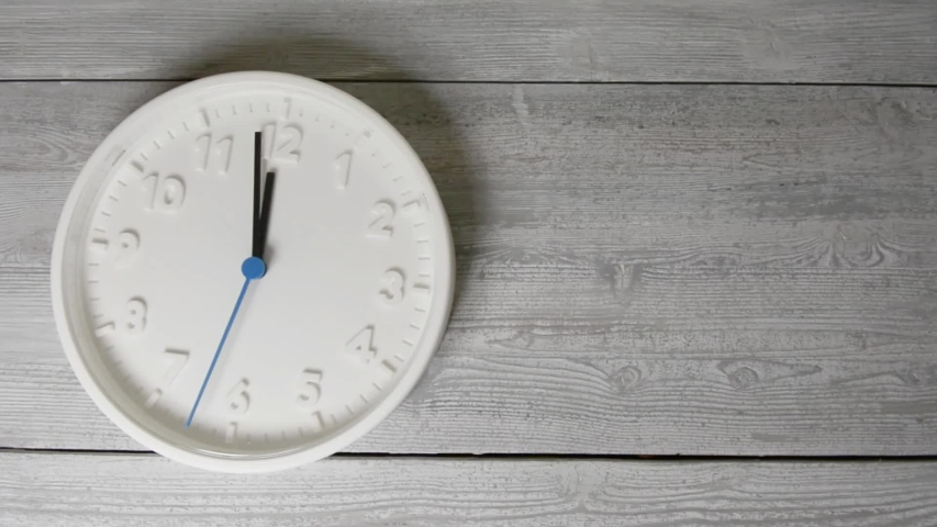 White clock on wooden surface.  Moving blue second hand   Shutterstock HD Video #1044955381