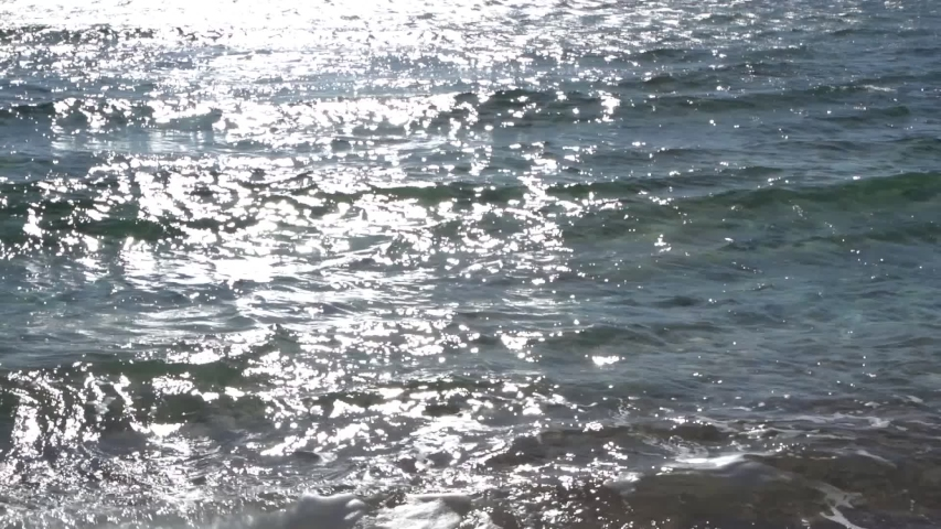 Beautiful sunny sparkling water video background. Slow motion footage of soft waves of sea splashing at sandy beach of Egypt. Abstract natural backdrop. | Shutterstock HD Video #1044957841