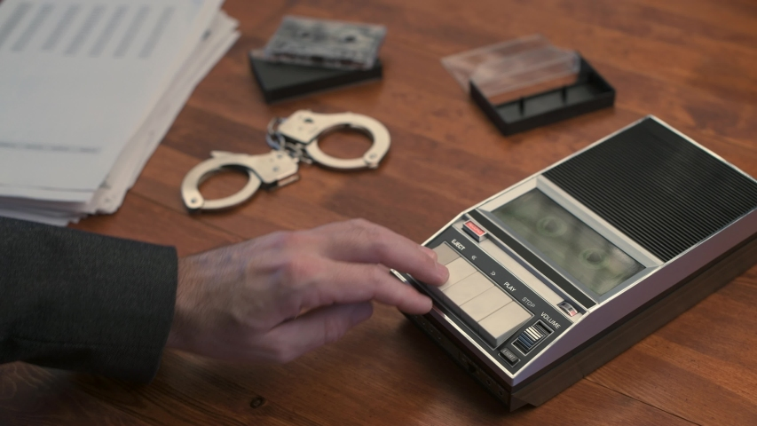 Police detective investigator playing audio cassette tape with recorded interview and interrogation statement   Shutterstock HD Video #1044971911