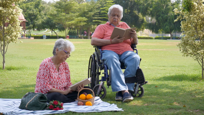 Elderly man and woman happily enjoying their picnic on Valentines's day in India. Retired couple sitting in a park and reading books, enjoying their peaceful valentine's picnic date together with h... | Shutterstock HD Video #1045012591