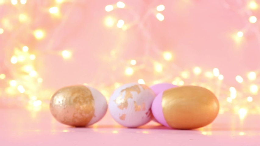Gold and pink eggs pattern on a light blurry garland. Shallow depth of field. Holiday concert | Shutterstock HD Video #1045027111