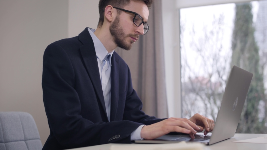 Portrait of young handsome Caucasian man looking out the window and typing on laptop keyboard. Confident businessman in suit and eyeglasses working online. Lifestyle, intelligence, wealth. | Shutterstock HD Video #1045058221