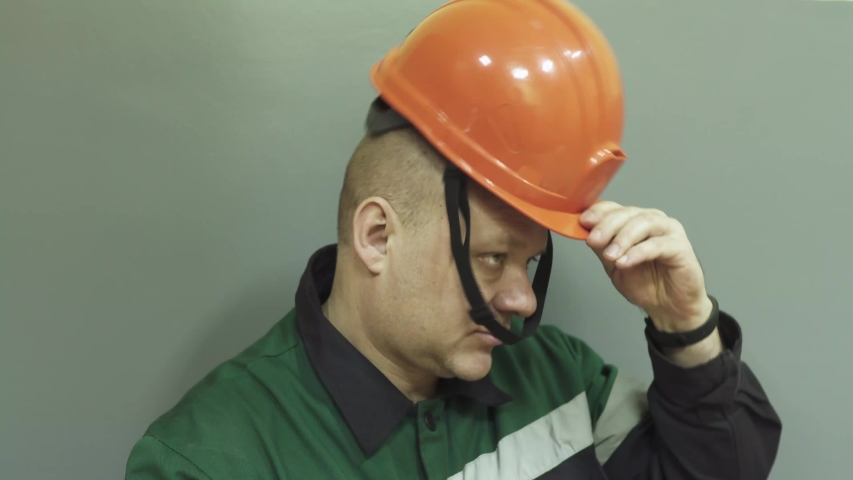The face of a man in a work uniform of an engineer at work. The engineer speaks on the radio, puts on a helmet, glasses, and turns on a flashlight.  | Shutterstock HD Video #1045091581