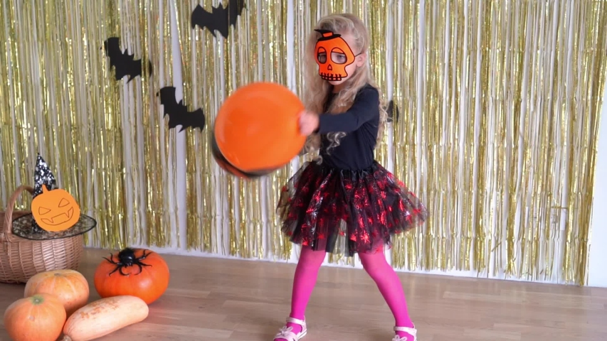 Preschooler girl with blond long curly hair playing with balloons at Halloween party. Active child have fun in room decorated with pumpkins and bats. Camera slow motion shot with gimbal. | Shutterstock HD Video #1045101841