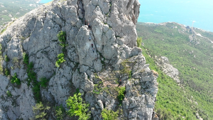 Aerial view of people climbing on rock. Summer sports and active lifestyle concept. Adrenaline, strength, ambition. Male rock climber training outdoor in summer. | Shutterstock HD Video #1045308181