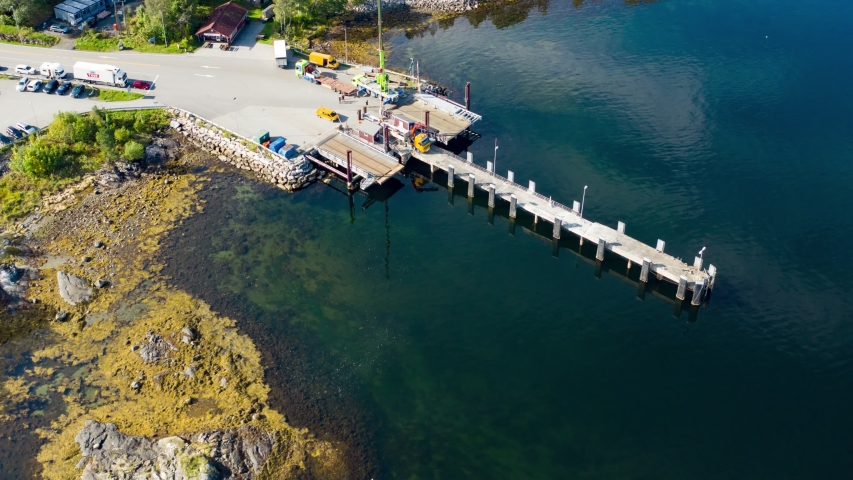 Bird's eye view of the Kanestraum ferry quay. Vehicles and passengers boarding the ferry on a beautiful sunny day. Waters are calm and clear. | Shutterstock HD Video #1045390591