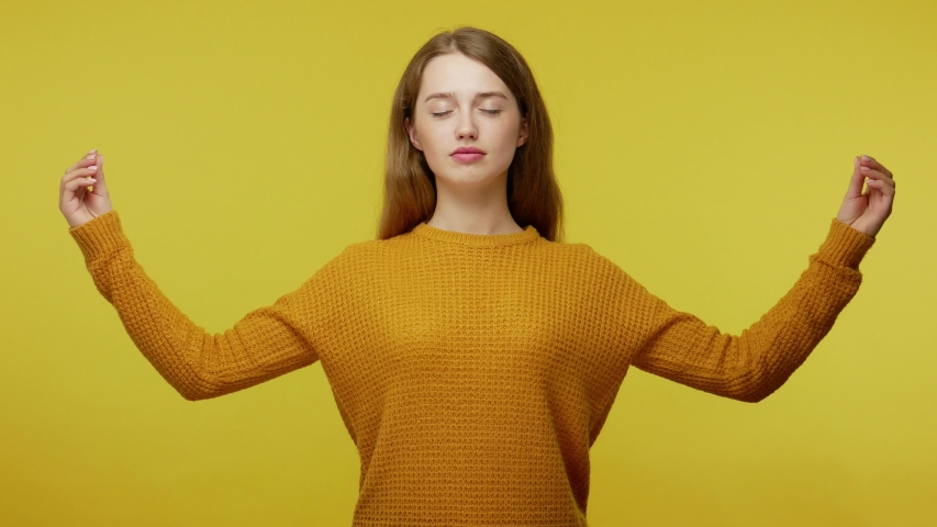Mindful yoga, harmony. Cute peaceful girl in pullover making mudra gesture with fingers and meditating with calm pacified expression, relaxation. indoor studio shot isolated on yellow background | Shutterstock HD Video #1045399861