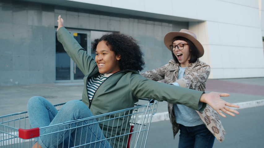 Happy attractive girls friends are riding shopping cart laughing outdoors near mall having fun together. Friendship, lifestyle and entertainment concept. | Shutterstock HD Video #1045402141