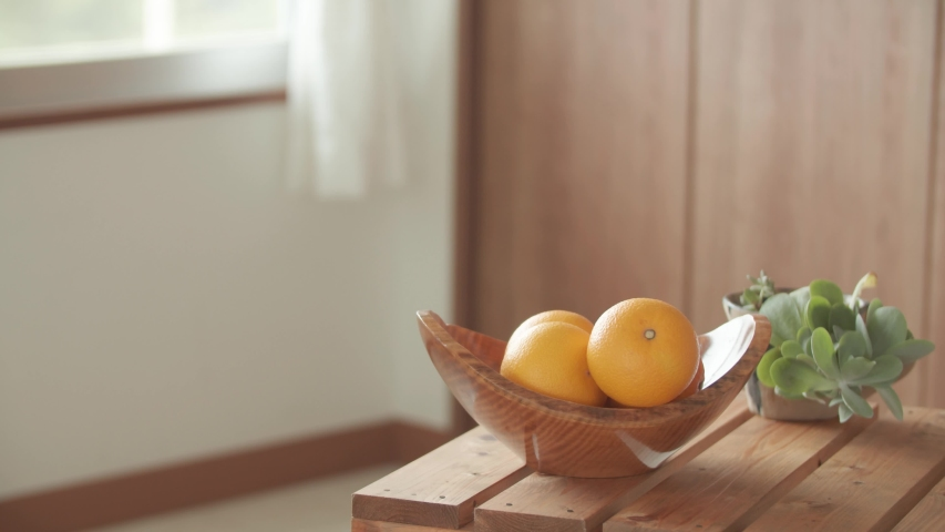Placing an orange from a wooden bowl on a wooden table by hand | Shutterstock HD Video #1045451341