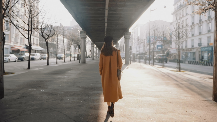 Back view of beautiful elegant tourist woman exploring Paris street under high line metro. City life concept slow motion | Shutterstock HD Video #1045899871