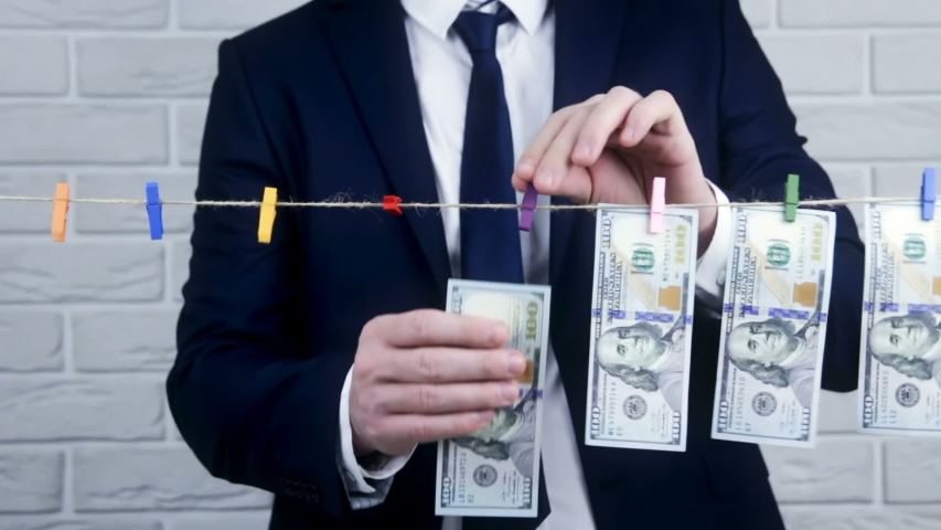 Man in the suit launder money. Businessman in suit drying money. Corruption. Money laundering.  | Shutterstock HD Video #1046376121