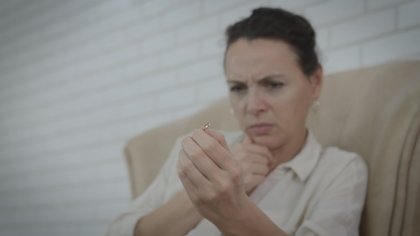 Think of divorce ring. Pensive woman with a ring think of her couple in the armchair. | Shutterstock HD Video #1046569081