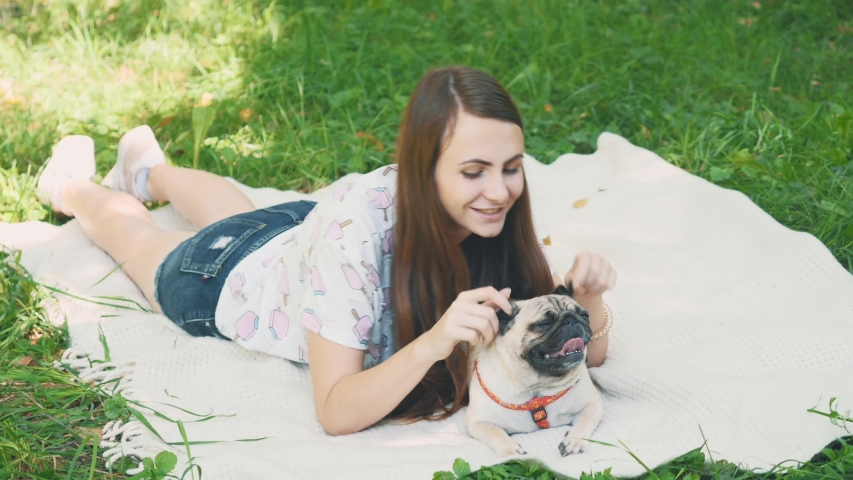 Smiling lady is taking free time with her dog. Woman relaxing in the nature with her little pug dog. Close up. Copy space. 4K. | Shutterstock HD Video #1046770951