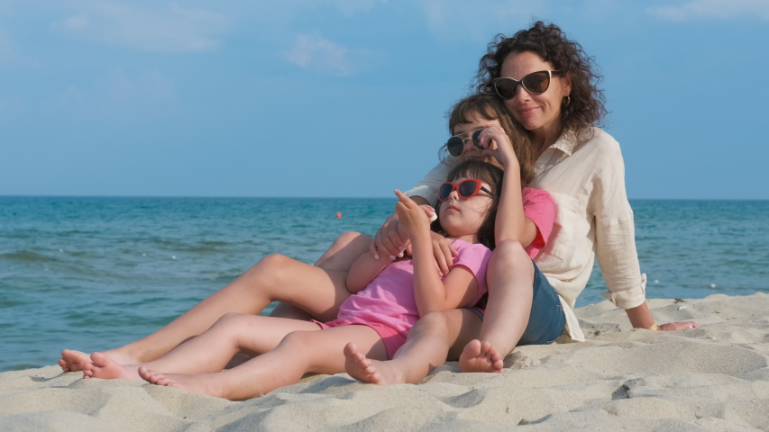 Woman with children on the beach. Woman with two daughters lay down on the sandy beach by the sea. | Shutterstock HD Video #1046778511