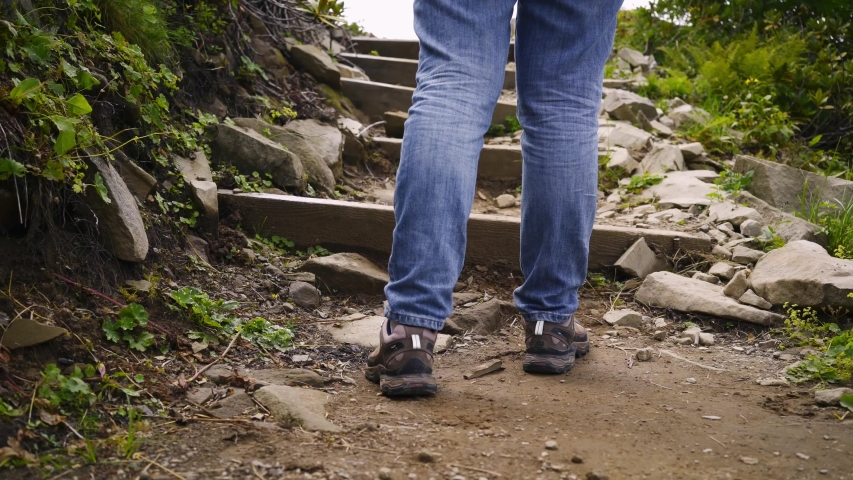 Happy girl traveller goes up stairs on rocky path in sunny day. Panorama shot from below upward from close-up stepping feet to cheerful lady with outstretched arms against high peak   Shutterstock HD Video #1046836981