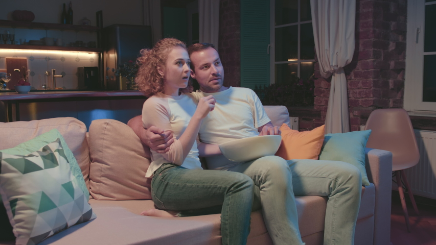 Young attractive girlfriend preparing popcorn and joining her boyfriend on couch watching movie together in evening. Happy young husband and wife spending evening watching tv. | Shutterstock HD Video #1046856391