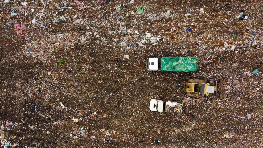 Landfill site with equipment aerial view. Garbage trucks unload garbage. A pile of household trash with soil. Garbage landfill, top view. Problems with household waste. | Shutterstock HD Video #1046904361