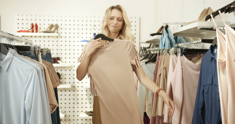 Stylish young blond Caucasian woman standing in clothing store and putting to herself stylish clothes on hangers instead of trying on. Prety female buyer shopping in fashion shop. | Shutterstock HD Video #1046966191