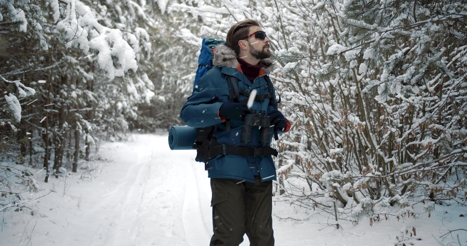 Mature bearded traveler in warm clothing carrying big backpack while walking in snowy forest during winter day. Male tourist enjoying favorite hobby with beautiful seasonal nature around. | Shutterstock HD Video #1047009361