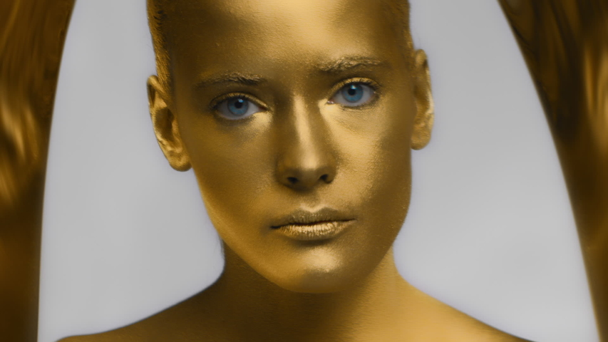 Gorgeous fashion model girl in golden coating open blue eyes and looking at camera, close up portrait. Sensual young woman with golden skin posing. Art design make up. Glitter metallic shiny makeup. | Shutterstock HD Video #1047018181