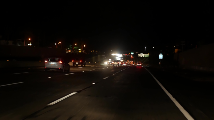 View from the car. Los Angeles busy freeway at night time. Massive Interstate Highway Road in California, USA. Auto driving fast on Expressway lanes. Traffic jam and urban transportation concept | Shutterstock HD Video #1047095611