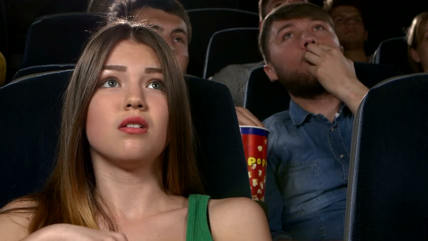 group of young people watching movie at cinema: thriller, all worry, eating popcorn. close-up - a girl. Behind - the cheerful company of young people. different ages