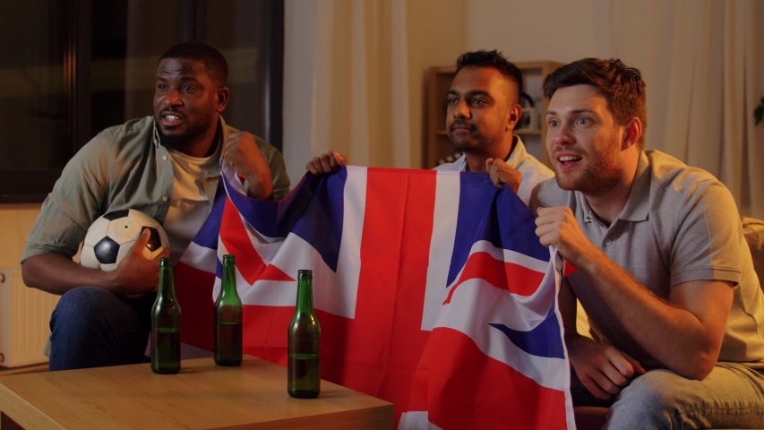 Friendship, sports and entertainment concept - happy male friends with soccer ball, british flag and beer football team at home | Shutterstock HD Video #1047212941